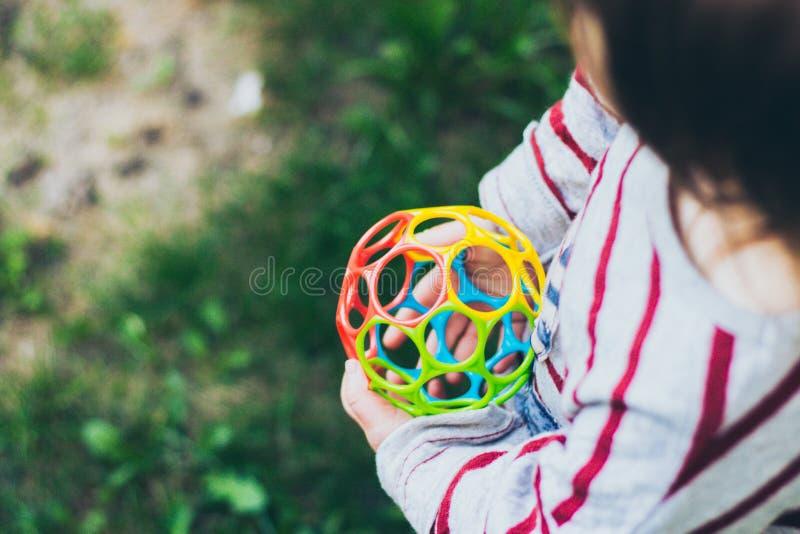 Menina pequena da criança que guarda a bola colorida imagem de stock