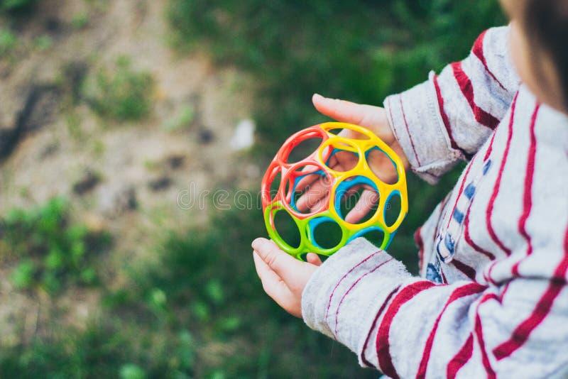 Menina pequena da criança que guarda a bola colorida imagens de stock