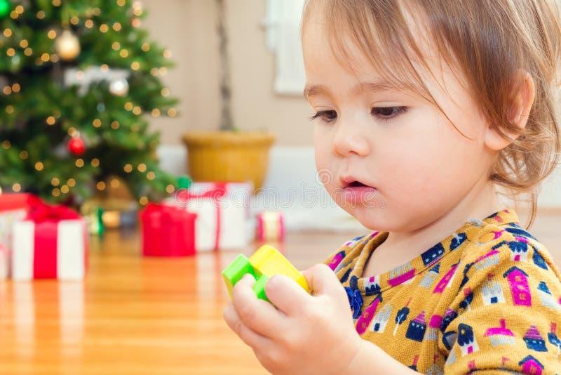 Menina pequena da criança que joga com seus brinquedos na frente da árvore de Natal imagens de stock royalty free
