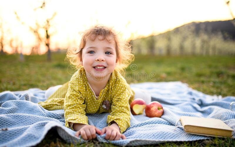 Menina pequena de criança sentada ao ar livre no cobertor na primavera, olhando para a câmera foto de stock royalty free