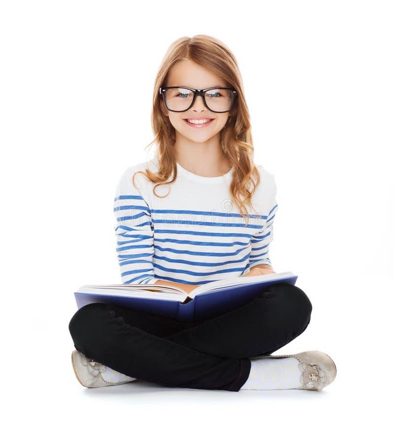 Menina pequena de sorriso do estudante que senta-se no assoalho foto de stock royalty free