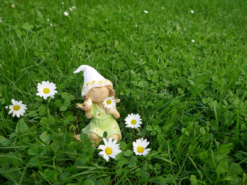 A menina pequena do anão com um pássaro em sua mão senta-se em um prado verde foto de stock