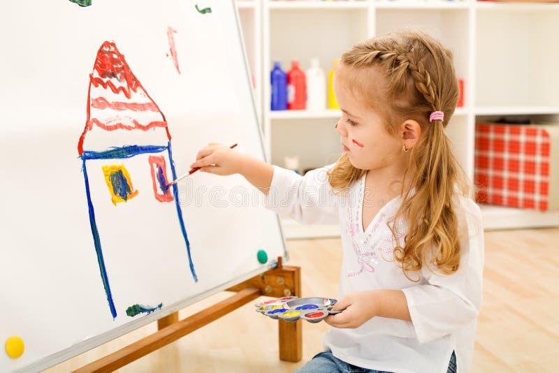 Menina pequena do artista com sua obra-prima imagens de stock royalty free
