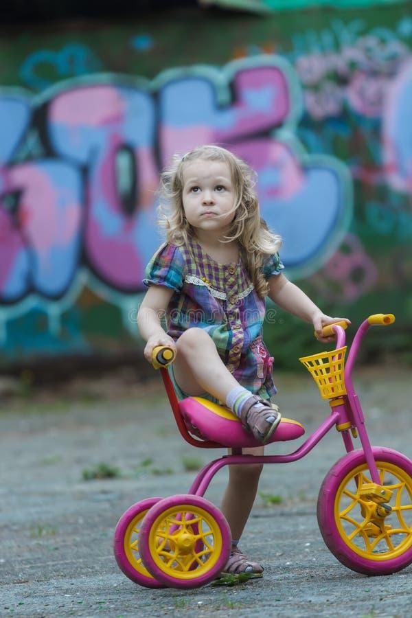 Menina pequena do ciclista que veste a túnica verificada que monta o triciclo amarelo e cor-de-rosa fotografia de stock