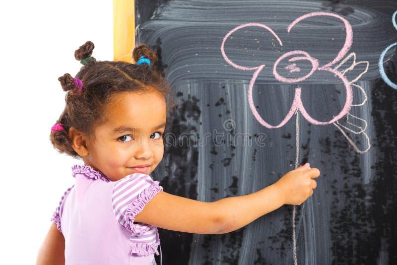 A menina pequena do mulato desenha na placa fotografia de stock