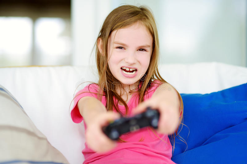 Menina pequena engraçada do preteen que joga com console do jogo fotos de stock royalty free