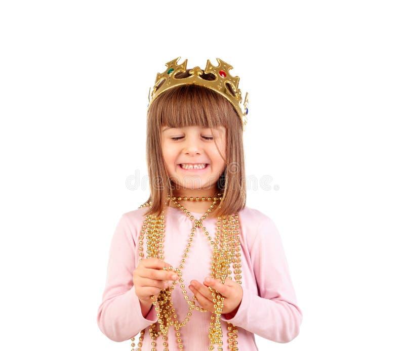 Menina pequena entusiasmado com coroa e a colar douradas foto de stock