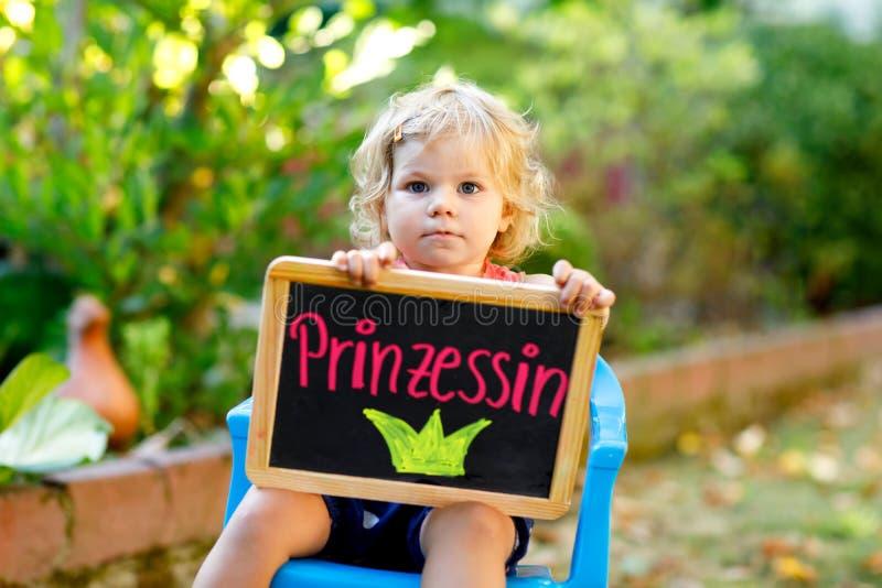 Menina pequena feliz da criança com a mesa do giz nas mãos A criança adorável saudável fora na mesa quando eu me cresço acima que imagens de stock