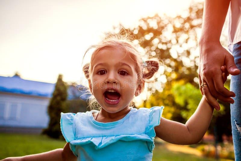 Menina pequena feliz da criança que ri e que grita fora Sira de mãe a guardar sua mão do ` s da filha no parque Tempo da família imagem de stock royalty free