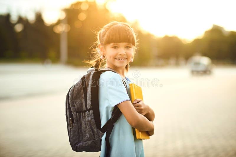 Menina pequena feliz do estudante com uma trouxa em sua maneira de educar fotografia de stock