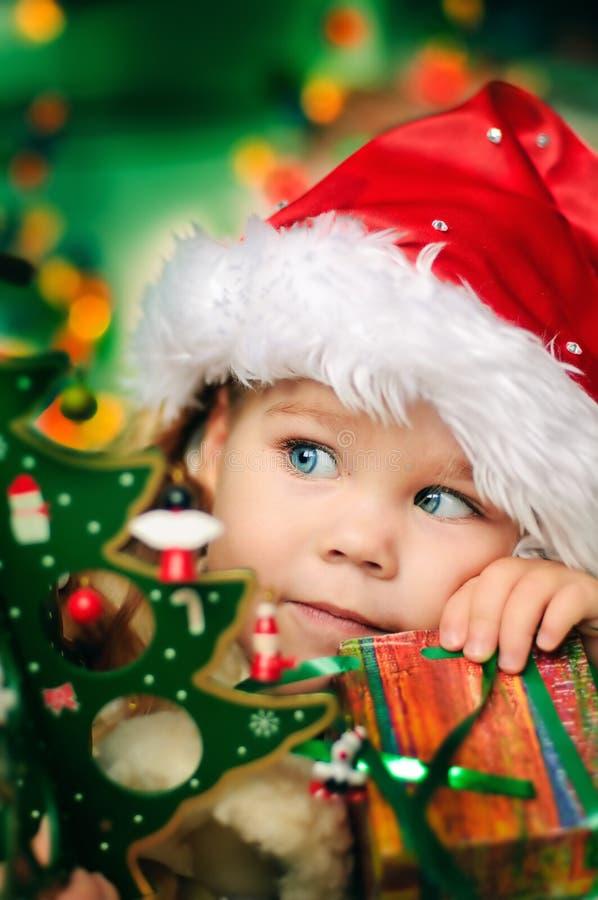 A menina pequena feliz no chapéu de Santa tem um Natal imagens de stock royalty free