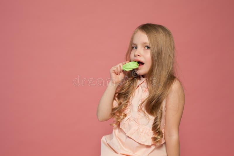 A menina pequena guarda à disposição uns doces doces do bolo do queque imagem de stock royalty free