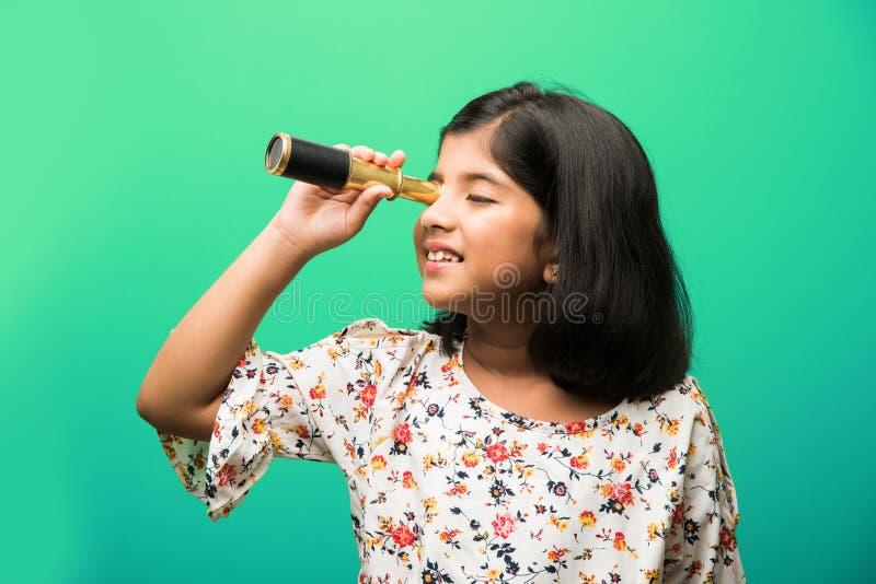 Menina pequena indiana que usa o telescópio e estudando a ciência espacial foto de stock