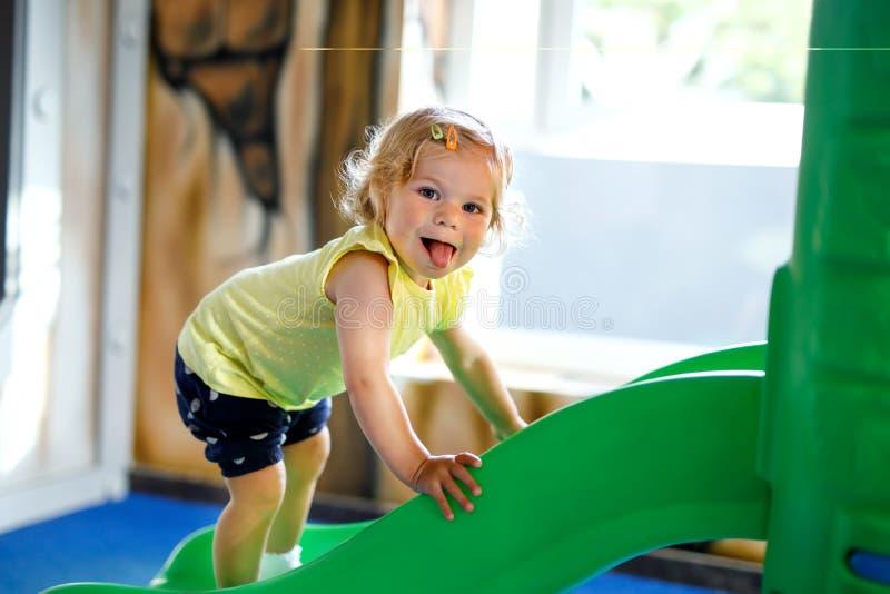 Menina pequena loura feliz da criança que tem o divertimento e que desliza no campo de jogos interno na guarda ou no berçário foto de stock royalty free