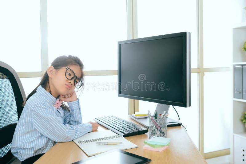 Menina pequena nova do negócio que senta-se na mesa de trabalho foto de stock