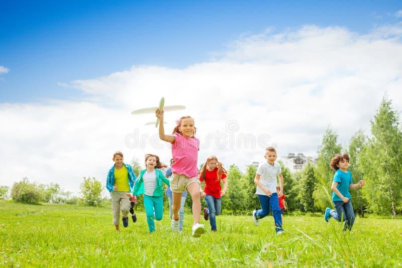 Menina pequena que guarda o brinquedo e as crianças do avião atrás fotografia de stock royalty free