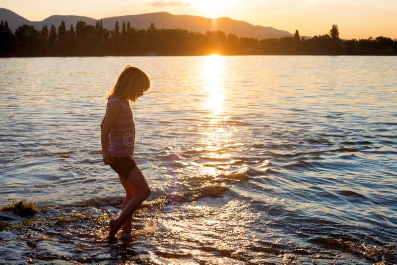 Menina pequena que joga na água do rio no por do sol fotografia de stock royalty free