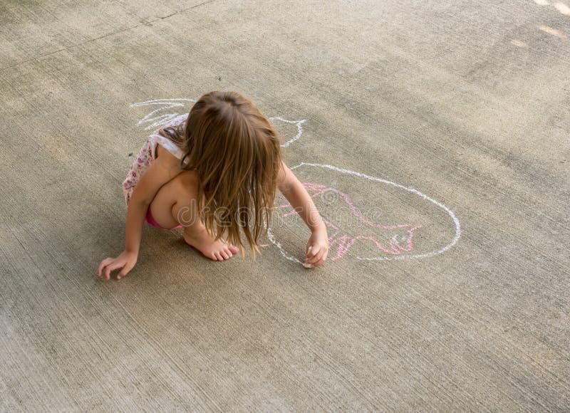 Menina pequena que tira um círculo em torno de um desenho de giz de um gato fotografia de stock royalty free
