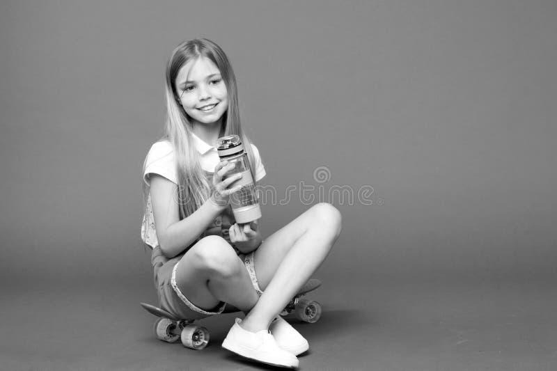 A menina pequena senta-se na placa do patim com a garrafa no fundo violeta Sorriso do skater da criança com garrafa de água Crian fotos de stock