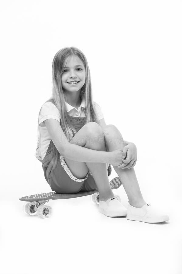 A menina pequena senta-se na placa do patim isolada no branco Sorriso do skater da criança com longboard Criança do skate no fato imagem de stock