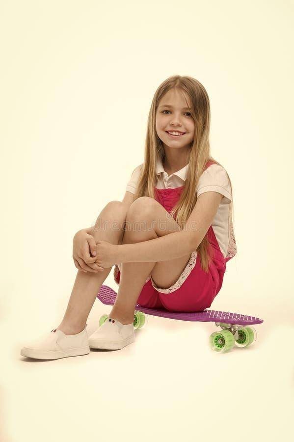 A menina pequena senta-se na placa do patim no branco Sorriso do skater da criança com longboard Criança do skate no fato-macaco  fotografia de stock royalty free
