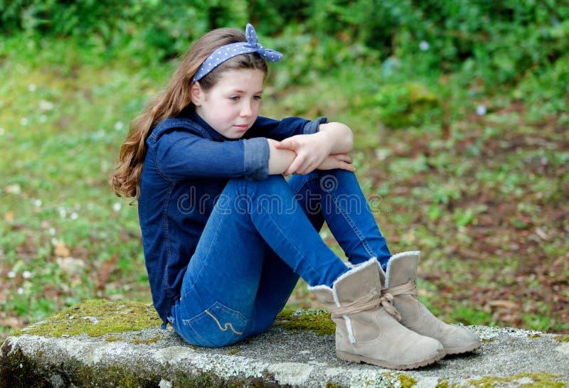 Menina pequena triste com dez anos de assento velho em um banco fotografia de stock