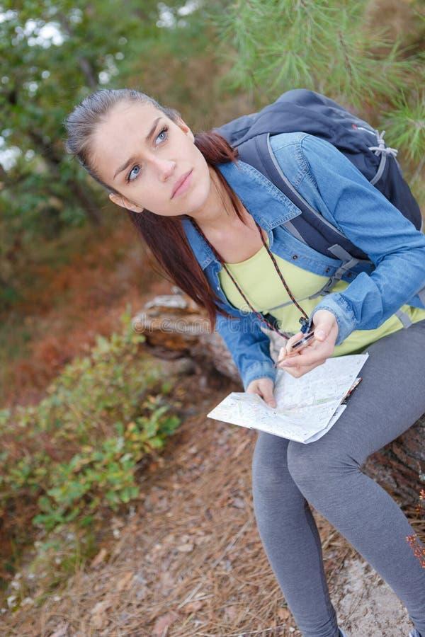 Menina perdida do caminhante com o mapa na estrada de floresta foto de stock royalty free