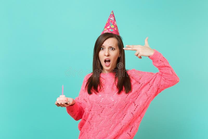 Menina perplexo nos dedos cor-de-rosa feitos malha do ponto do chapéu do aniversário da camiseta a dirigir como se se dispara apr fotos de stock