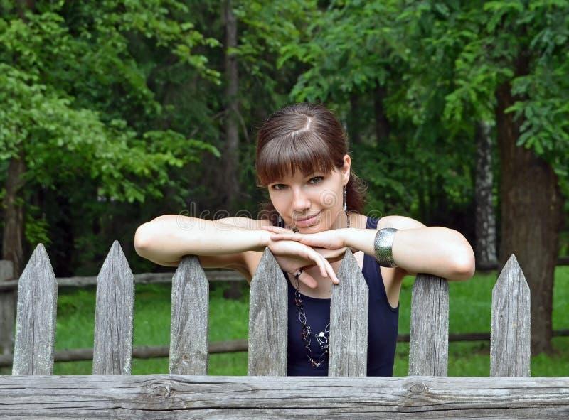Menina perto da cerca rural do vintage foto de stock