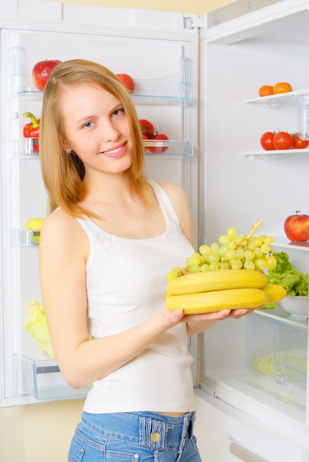 Menina perto do refrigerador imagens de stock