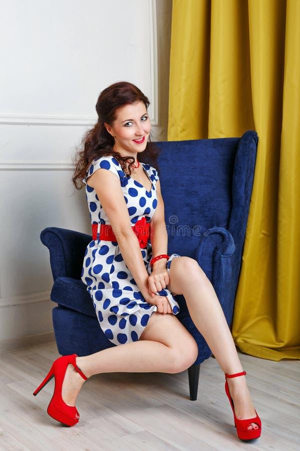A menina Pin-acima em um vestido e em sapatas senta-se em uma cadeira fotos de stock