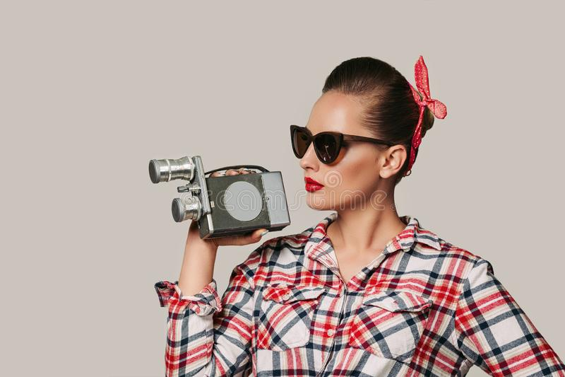 Menina Pin-acima na camisa de manta que guarda a câmera velha do vintage imagem de stock royalty free