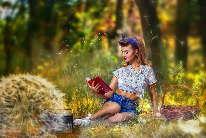 Menina Pin-acima no piquenique que lê um livro no fundo da floresta e em dentes-de-leão com uma cesta e um rádio imagem de stock royalty free