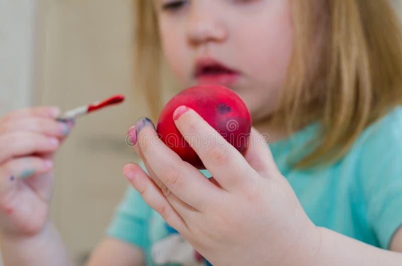 A menina pinta o ovo da páscoa fotos de stock royalty free
