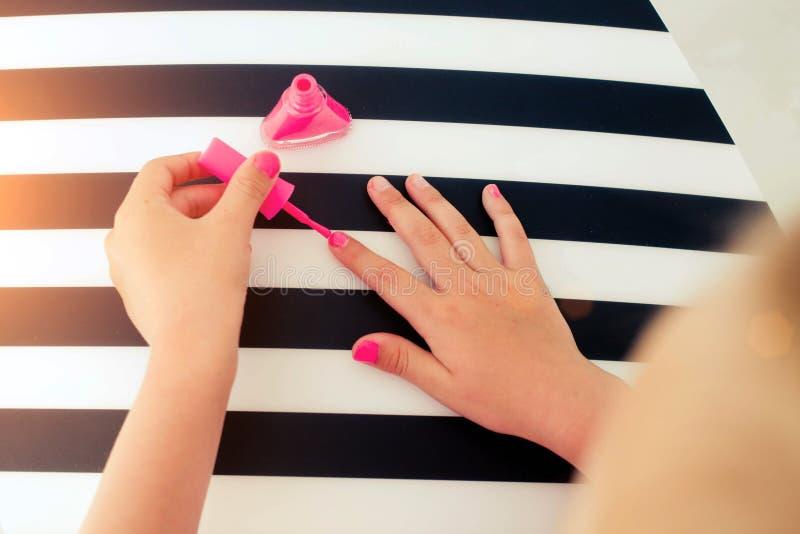 A menina pinta o verniz de prego cor-de-rosa dos pregos fotos de stock royalty free