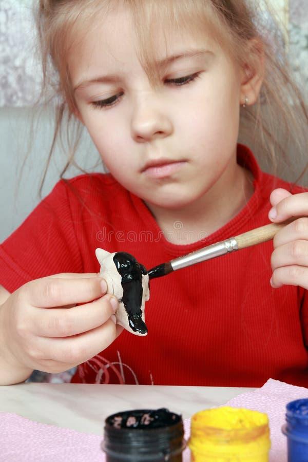 A menina pinta ofícios fotografia de stock