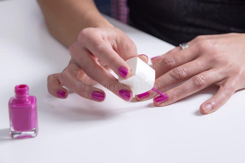 A menina pinta seus pregos com verniz para as unhas cor-de-rosa fotos de stock
