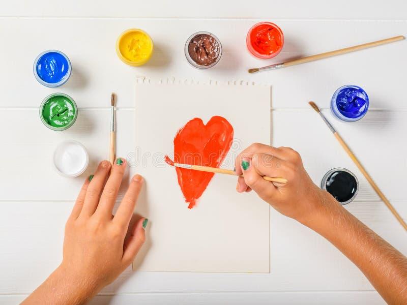 A menina pinta um coração vermelho em uma folha de papel em uma tabela de madeira branca Configuração lisa imagens de stock