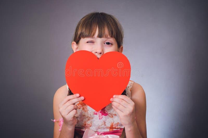 A menina pisc um olho e fecha um coração da boca imagem de stock