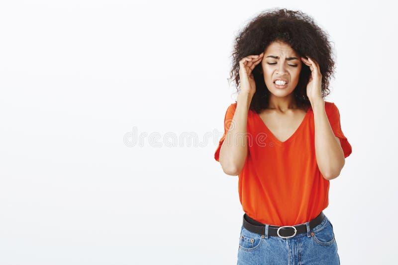 Menina pobre que tem a dor de cabeça terrível Tiro do estúdio da fêmea europeia com corte de cabelo afro, templos tocantes da vir imagens de stock