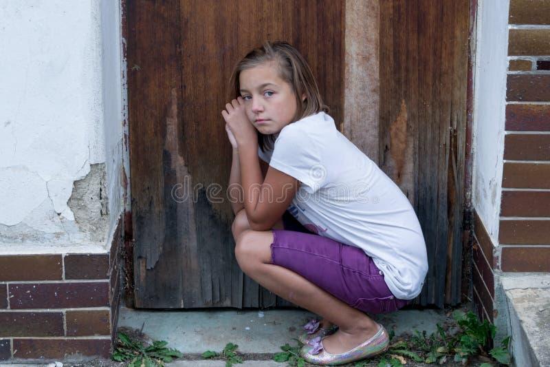 Menina pobre triste na frente da porta imagens de stock royalty free