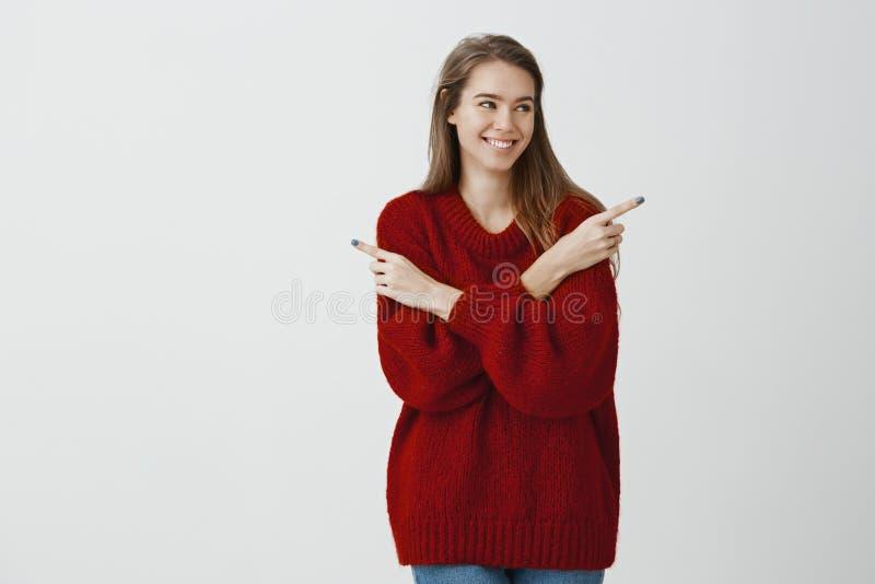 Menina popular atrativa que faz a decisão em que data vai Mulher caucasiano alegre satisfeito na camiseta na moda fraca vermelha fotografia de stock royalty free
