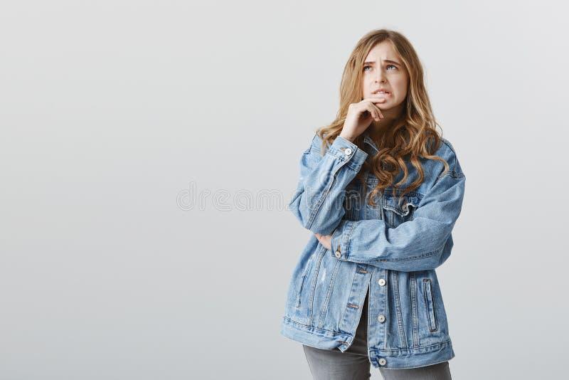 Menina popular não boa na matemática Mulher loura bonito incomodada confusa em dedo cortante do revestimento à moda da sarja de N fotos de stock royalty free