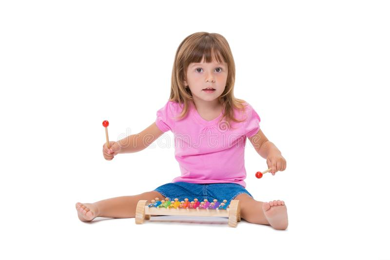 Menina positiva alegre de sorriso bonito 3 anos de jogo velho com o xilofone do brinquedo do instrumento musical isolado no fundo imagem de stock