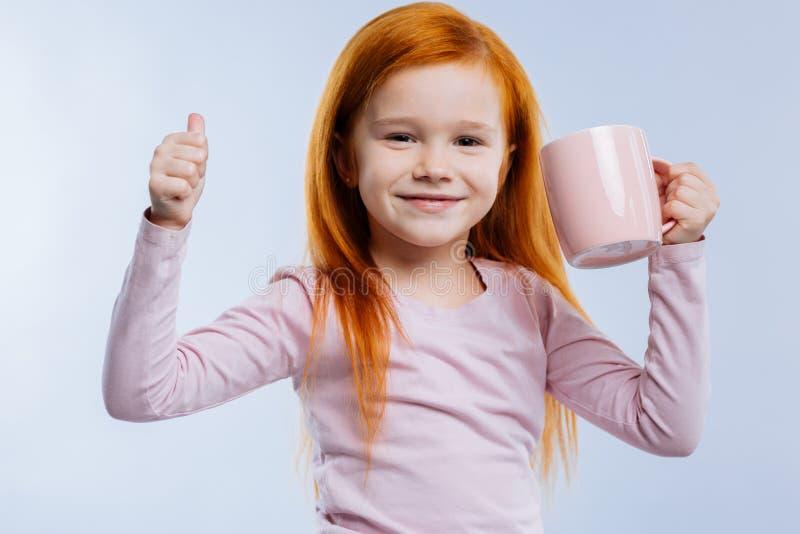 Menina positiva alegre que mostra lhe o sinal APROVADO fotografia de stock royalty free