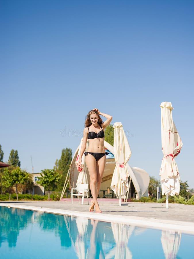 Menina positiva, bonita em um biquini que anda em um fundo da piscina Conceito do recurso Copie o espaço fotografia de stock royalty free