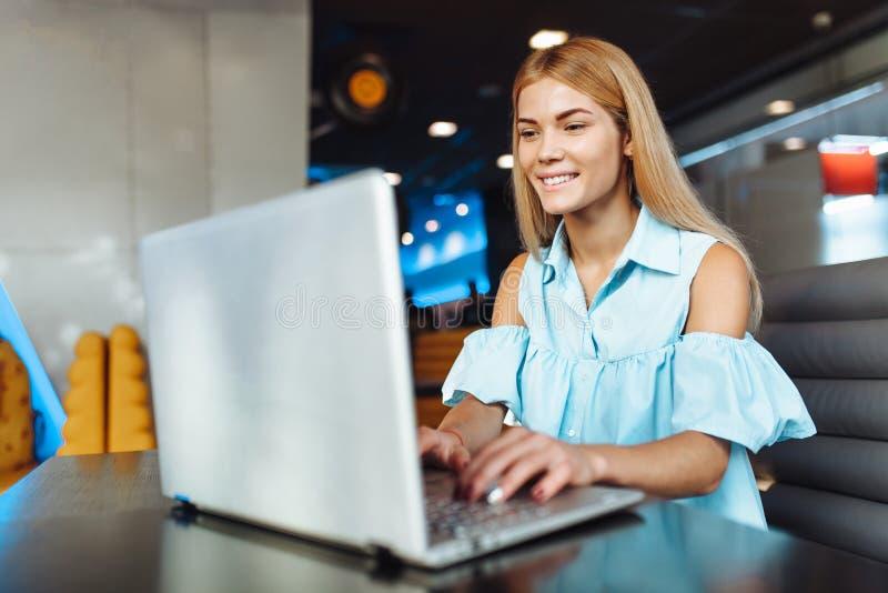 Menina positiva bonita que trabalha em um portátil, comprando sobre o I imagem de stock royalty free