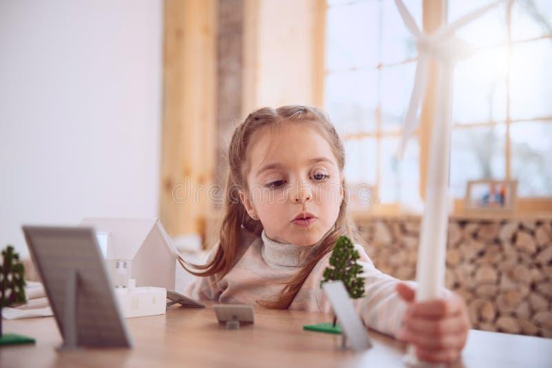 Menina positiva bonito que guarda um modelo do moinho de vento imagens de stock royalty free