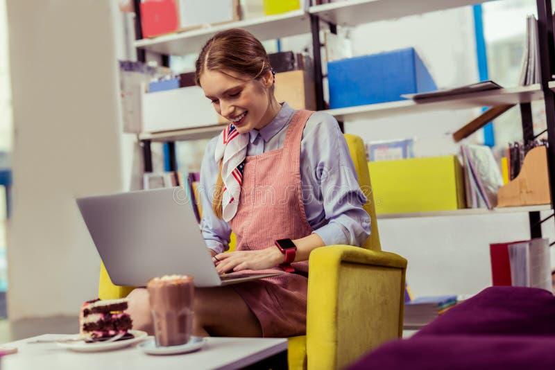 Menina positiva de sorriso com o relógio eletrônico em seu pulso fotos de stock royalty free