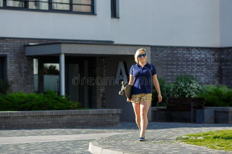 Menina positiva do tamanho com um passeio do longboard foto de stock